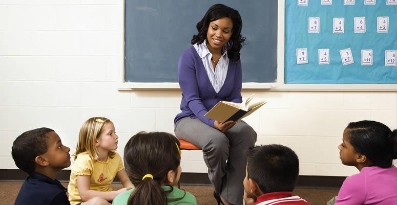 preschool teacher reading a book to class